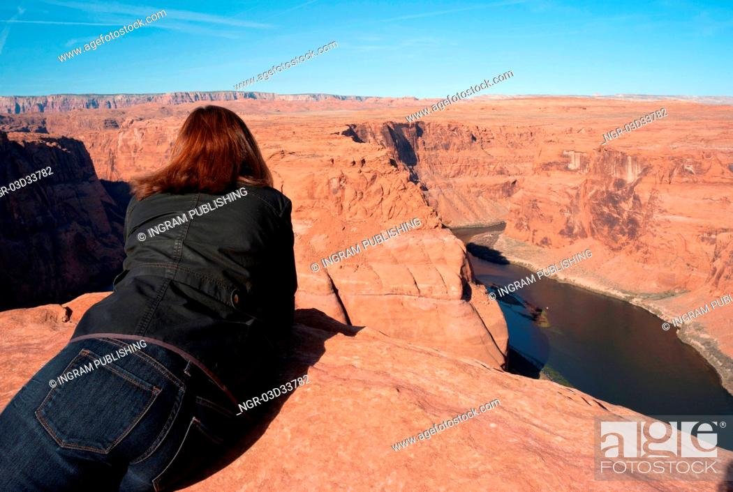 Stock Photo: Woman leaning on rock looking at a view, Horseshoe Bend, Glen Canyon National Recreation Area, Arizona-Utah, USA.