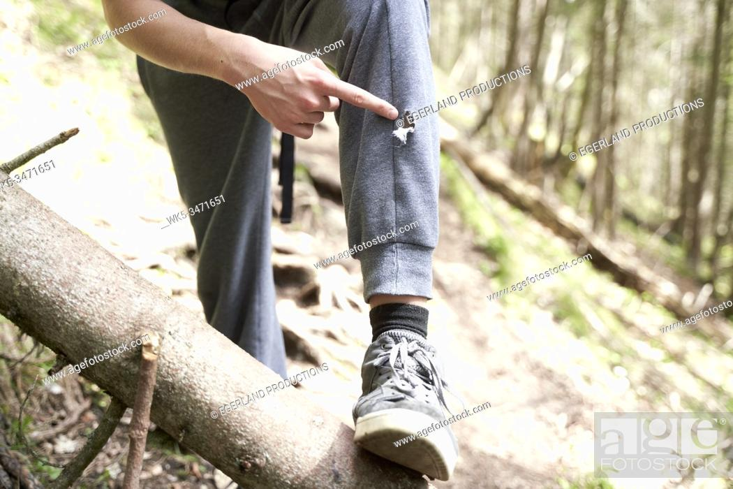 Stock Photo: Young boy in forest, pointing at a rip on his trousers. Bad Tölz, Upper bavaria, Germany.