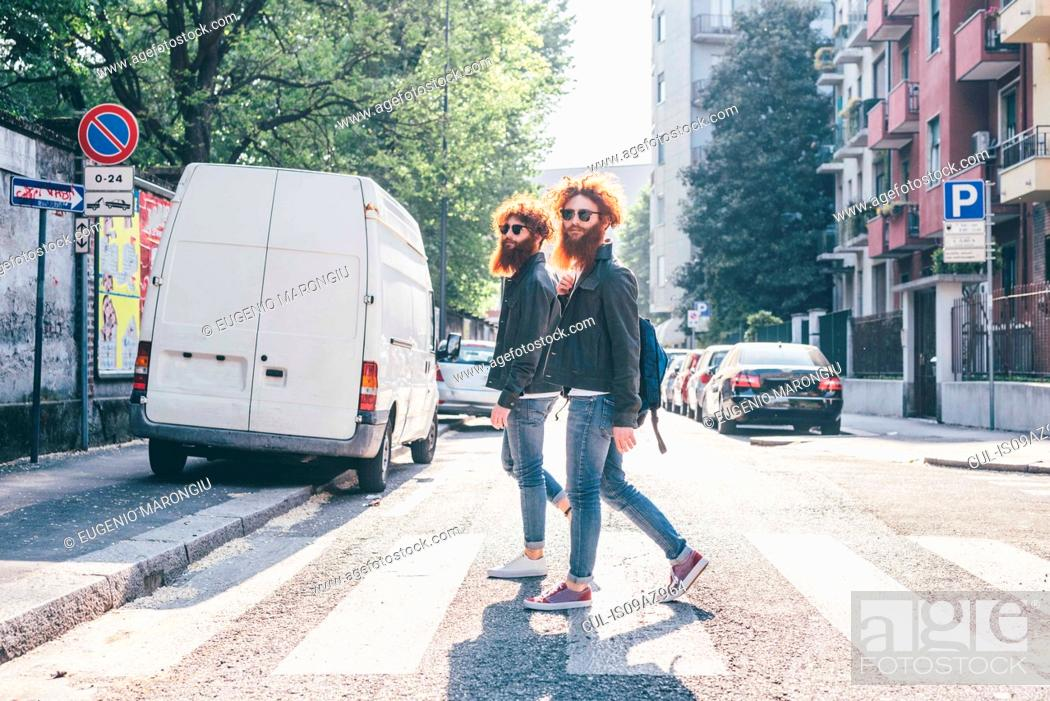Imagen: Young male hipster twins with red hair and beards strolling on pedestrian crossing.