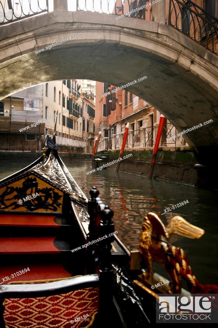 Stock Photo: Close up of part gondola with canal bridge in distance, Venice, Veneto, Italy.
