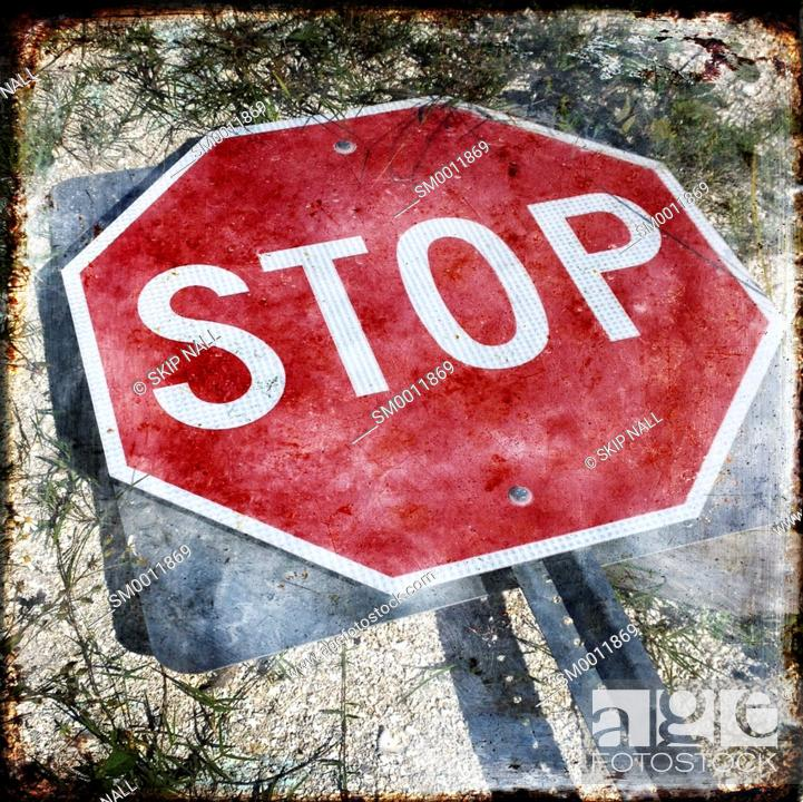 Stock Photo: A stop sign laying on the ground.