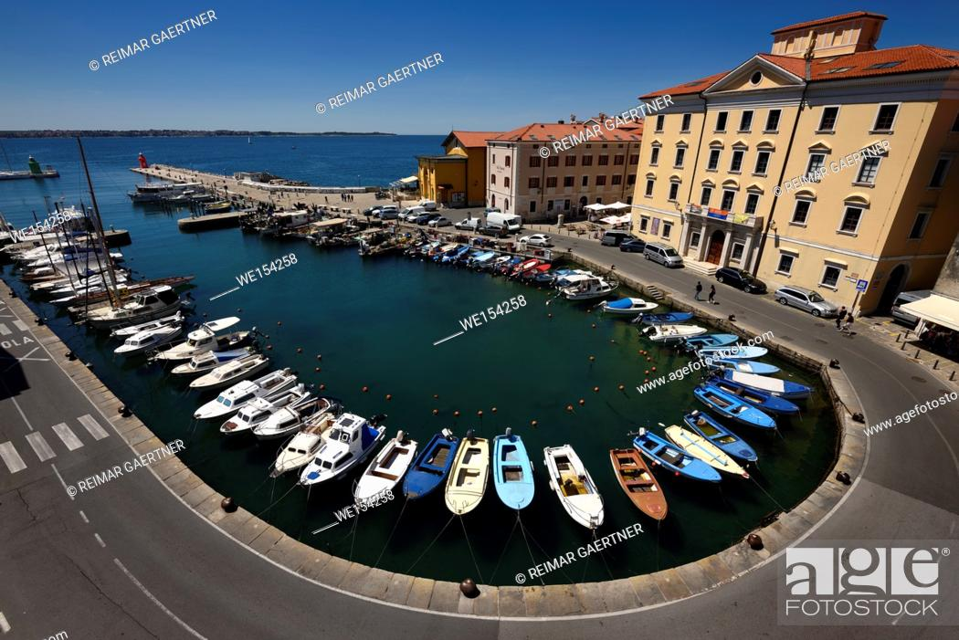 Stock Photo: Horseshoe pattern of moored boats at the inner harbour of Piran Slovenia on the Adriatic Sea coast with blue sky.