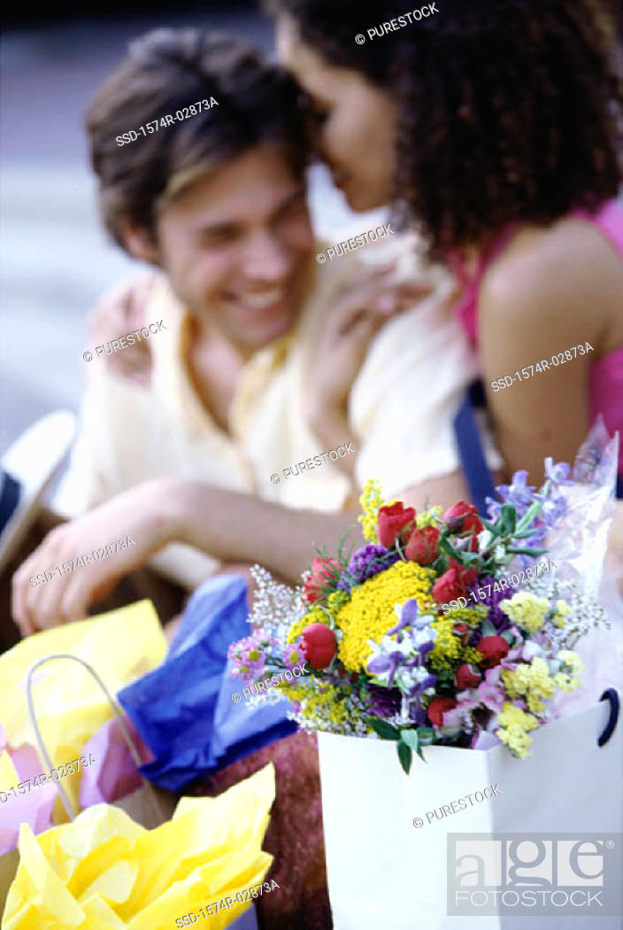 Stock Photo: Young couple sitting on the sidewalk with shopping bags.