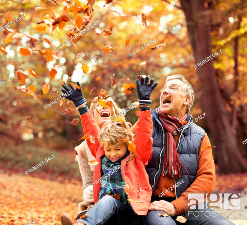 Stock Photo: Older couple playing with grandson in autumn leaves.