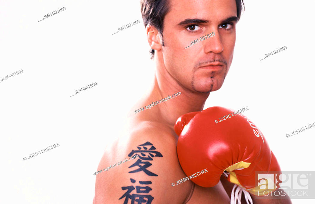 Stock Photo: Portrait of a young man, 20-25 25-30 30-35 years old, dark-haired, masculine, athletic and beautiful, stripped to the waist, with boxing gloves.