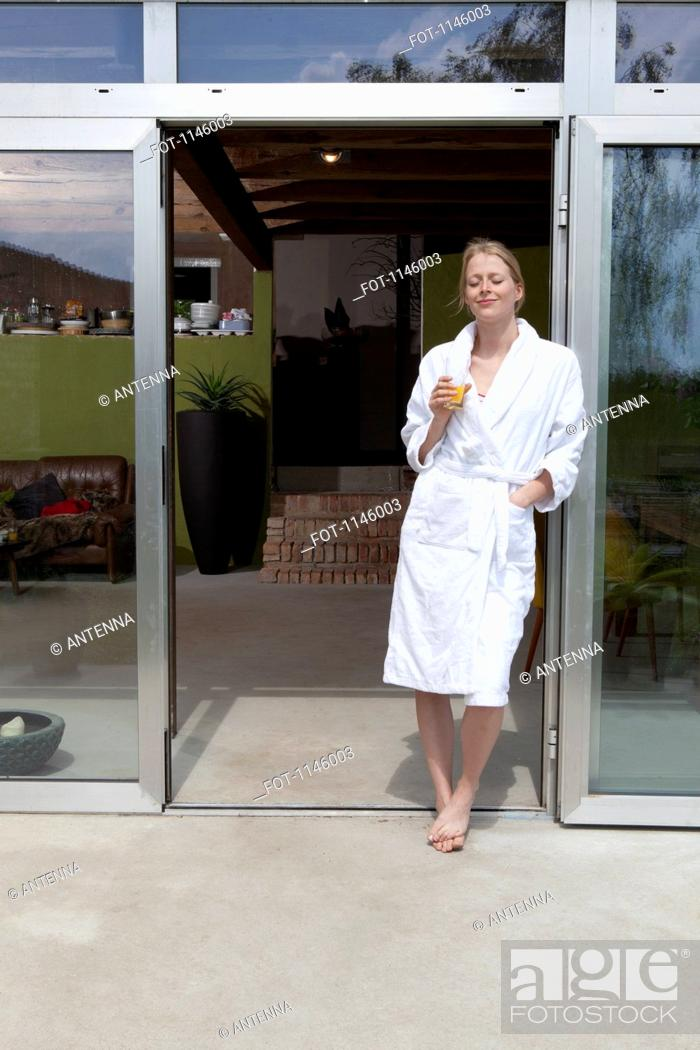 Stock Photo: A woman standing in the doorway of her house in a bathrobe enjoying the morning.