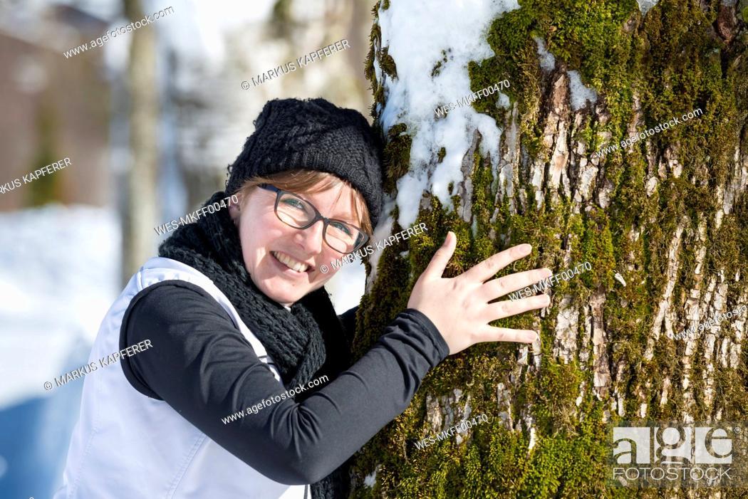 Photo de stock: Portrait of smiling woman hugging a tree in winter.