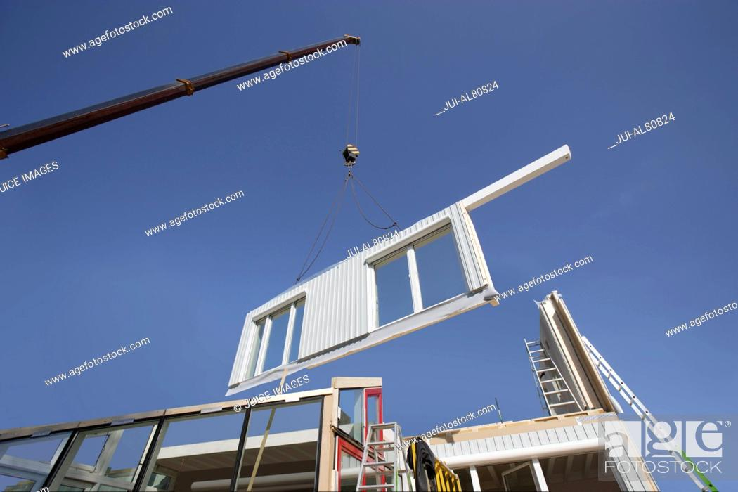 Stock Photo: Crane assembling pieces of a house.