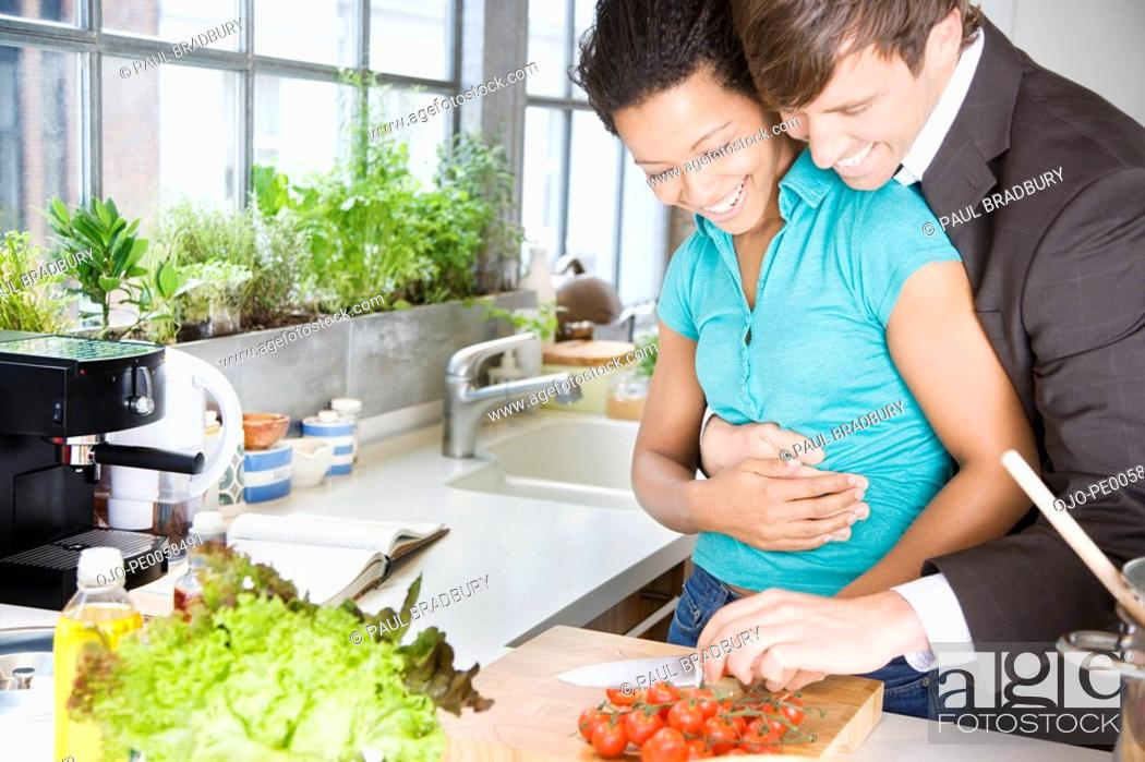 Stock Photo: Couple embracing in a kitchen chopping cherry tomatoes.
