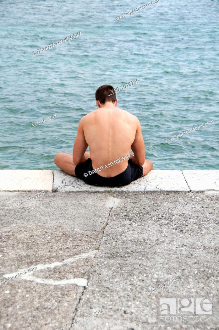 Stock Photo: man resting at Paquis Plage, Geneva Lake, Geneva, Switzerland.