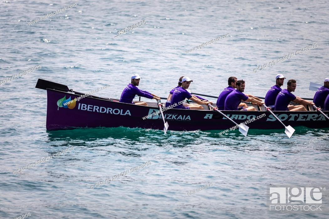 Stock Photo: CASTRO URDIALES, SPAIN - JULY 15, 2018: Competition of boats, regata of trainera, Santurtzi Iberdrola boat in action in the VI Bandera CaixaBank competition.