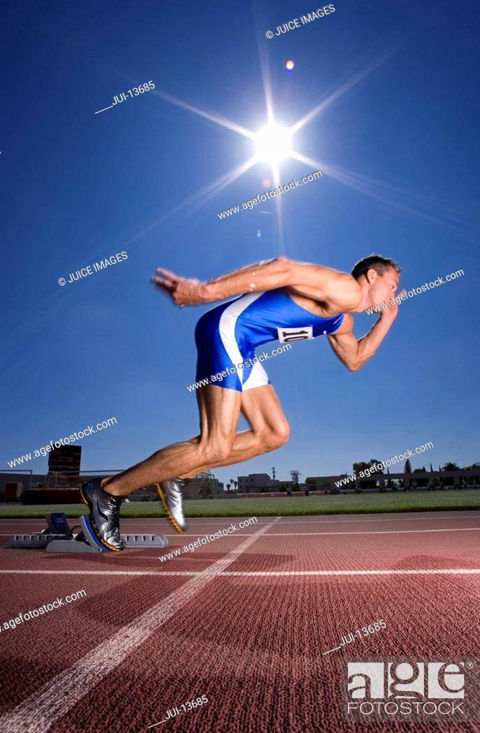 Stock Photo: Male sprinter leaving starting block, side view sun flare.