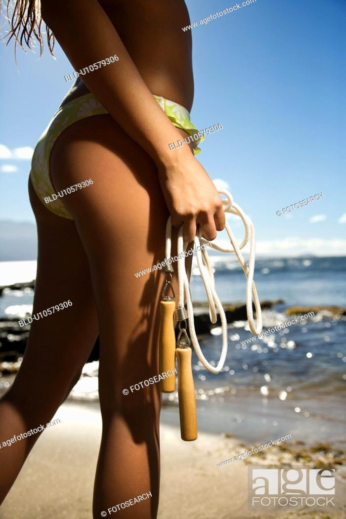 Stock Photo: Female holding jump rope in swimsuit on beach.