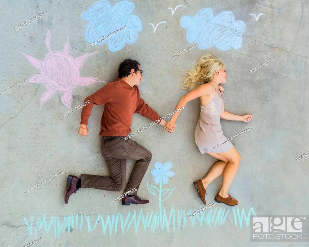 Stock Photo: Caucasian couple posing over sidewalk chalk drawing.