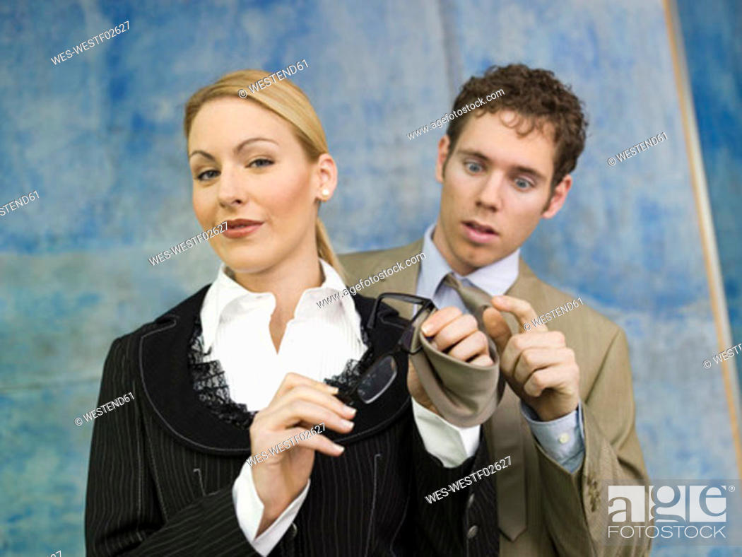 Stock Photo: Business woman cleaning spectacles with man's tie.