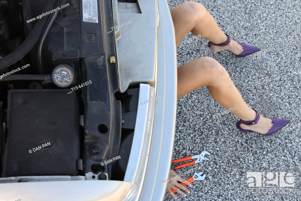 Stock Photo: Woman in purple high heels getting under a car fixing it only show her legs, hands and tools.
