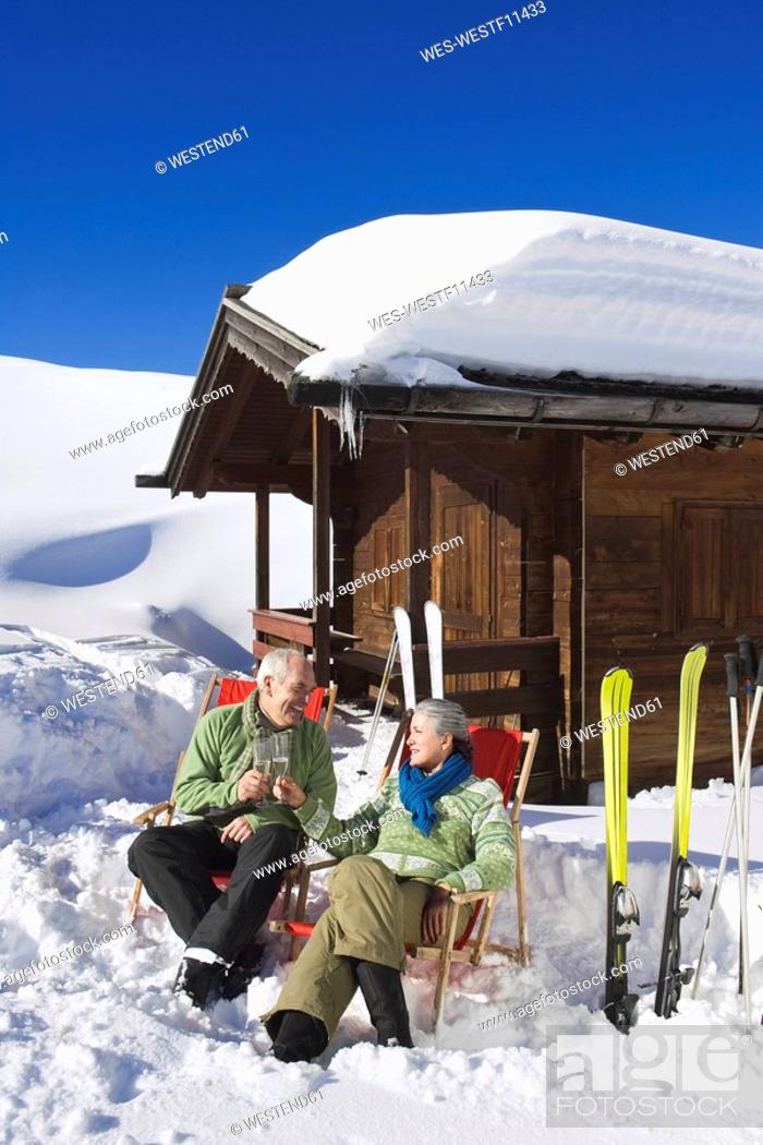Stock Photo: Italy, South Tyrol, Seiseralm, Senior couple sitting in front of log cabin, holding champagne glasses.