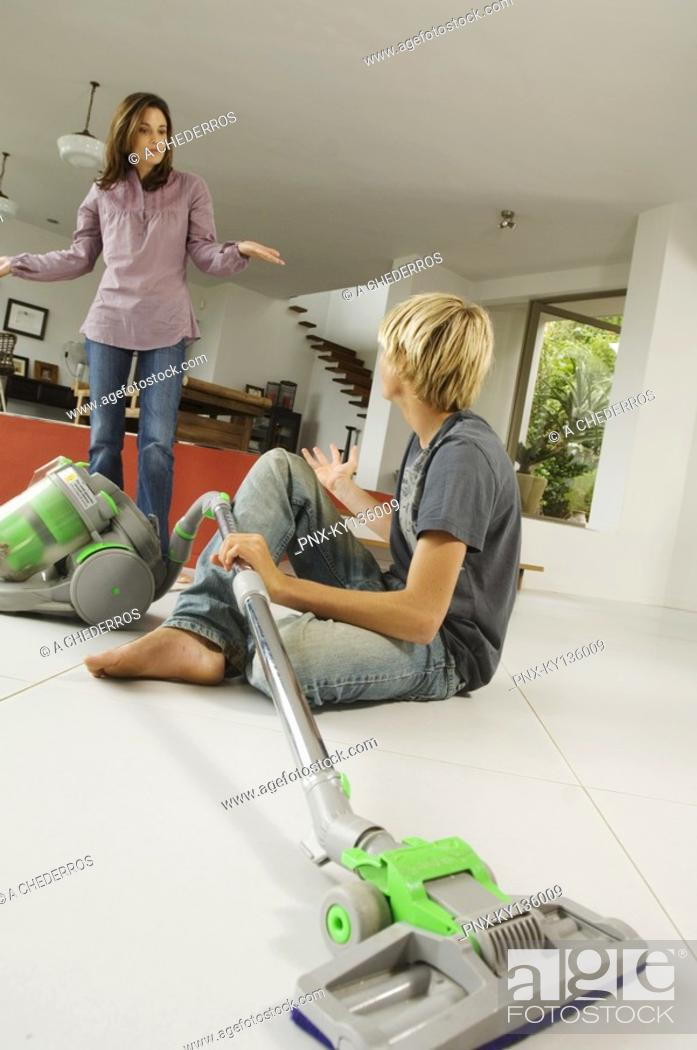 Stock Photo: Mother and son in living room, vacuum cleaner, indoors.