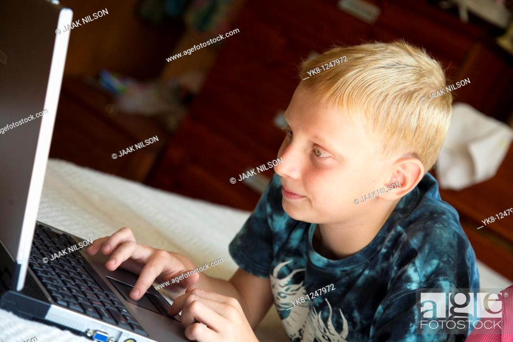 Stock Photo: Teenage Boy Lying Down and Using Laptop Computer.
