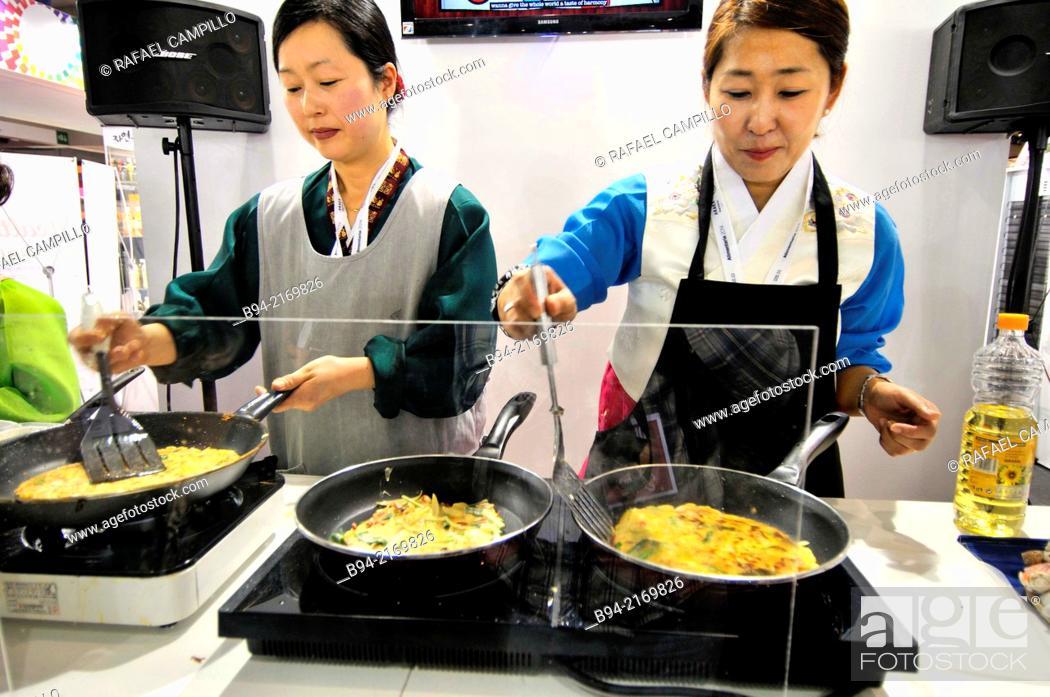 Stock Photo: Cooks preparing chinese food in Alimentaria, International Food and Drinks Exhibition, Fira de Barcelona. L'Hospitalet de Llobregat, Barcelona, Catalonia, Spain.