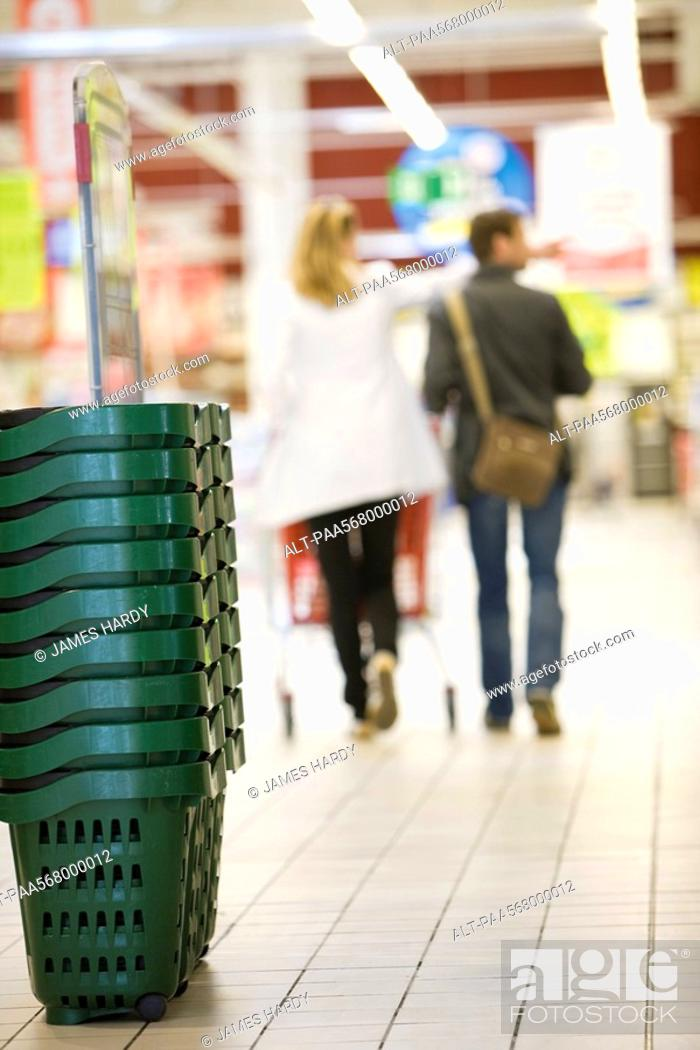 Stock Photo: Stack of shopping baskets, shoppers in background.
