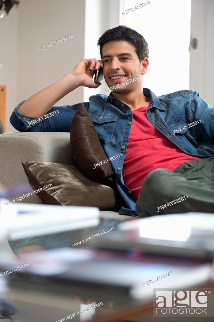 Stock Photo: Man reclining on a couch and talking on a mobile phone.