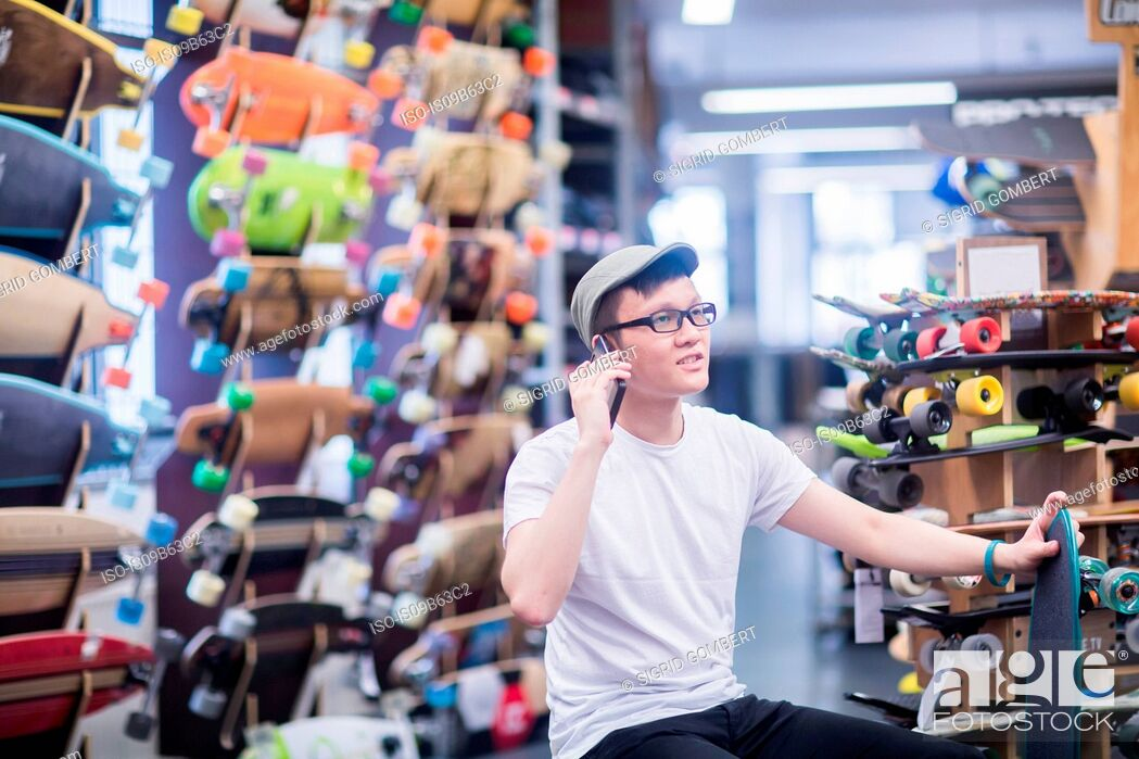 Photo de stock: Young male skateboarder making smartphone call in skateboard shop.