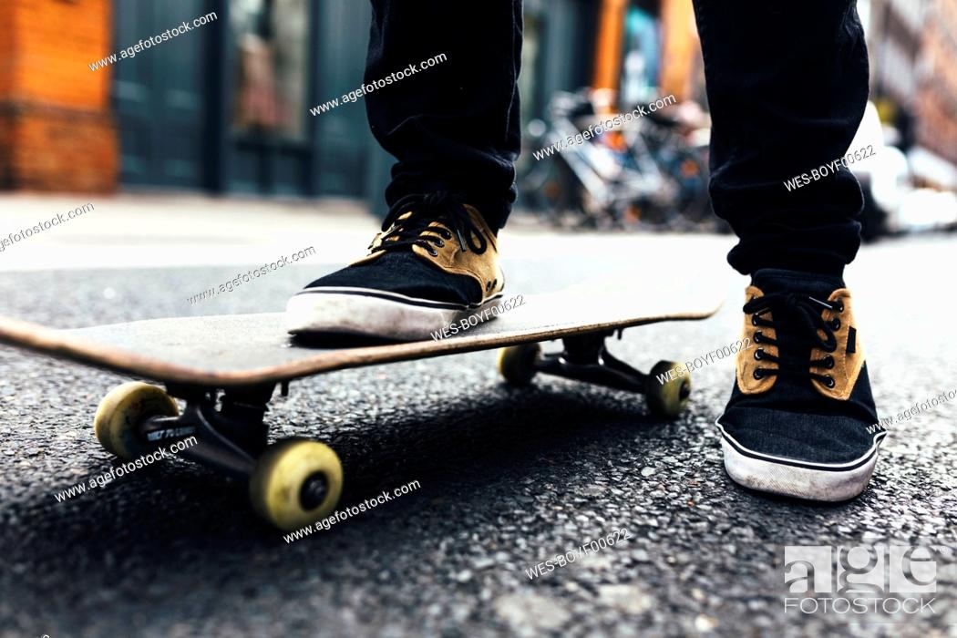 Photo de stock: Young skateboarder on the street, partial view.