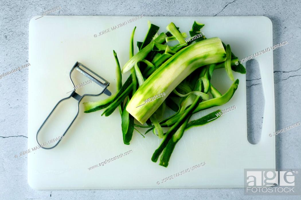 Photo de stock: Grated zucchini on cooking board with kitchen grater.