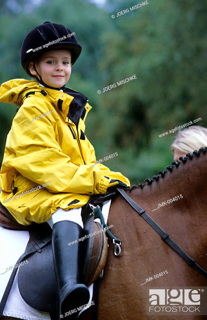 Stock Photo: A little girl, 5-10 years old, riding a horse at a horse show.