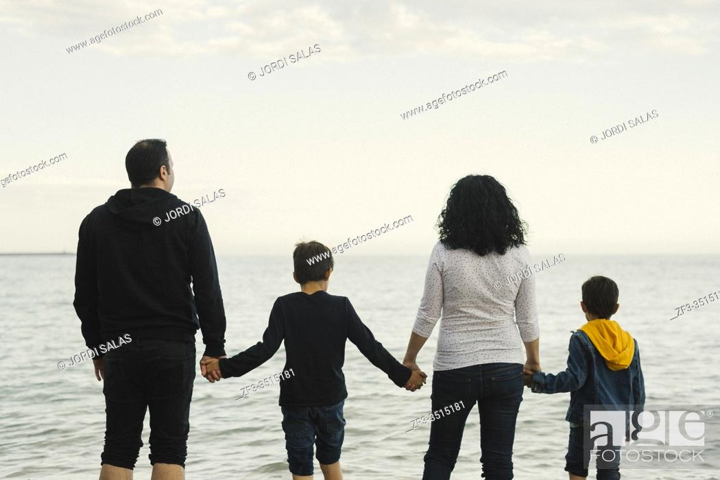 Stock Photo: Family of four members standing on the beach and watching at the sea.