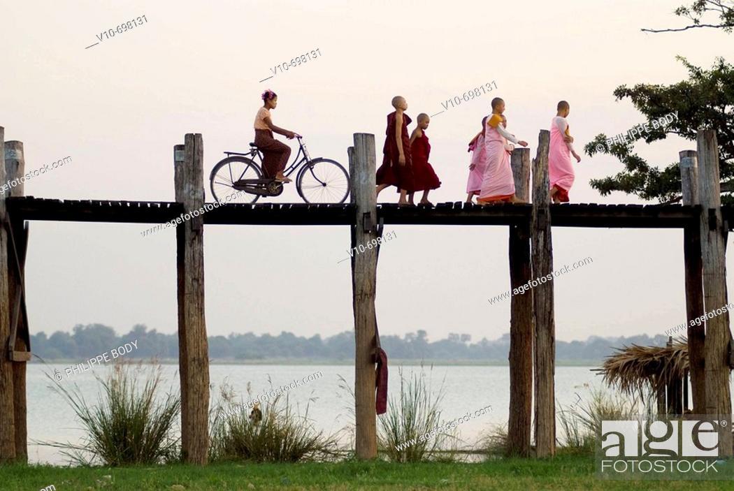 Stock Photo: Buddhist monks and nuns on the U Bein bridge in teak wood in the old royal city of Amarapura near Mandalay, Myanmar.