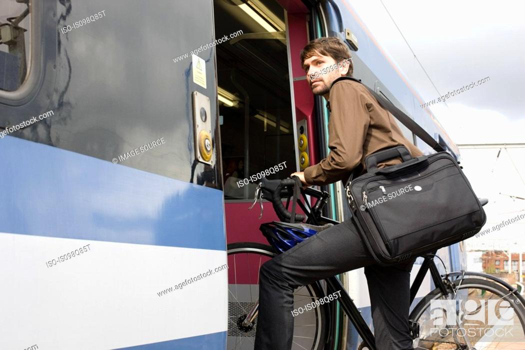 Stock Photo: Man with bike getting onto train.