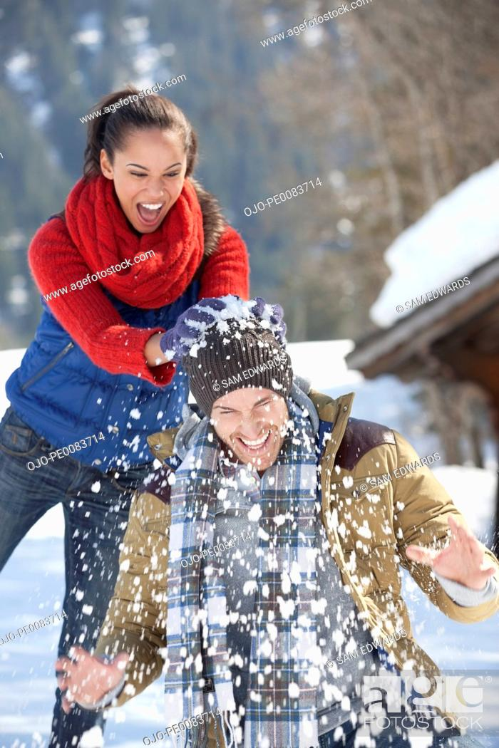 Stock Photo: Woman breaking snowball over man's head.