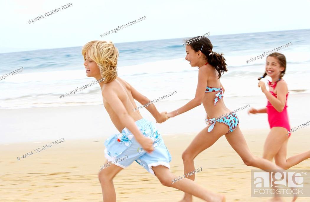 Stock Photo: Children holding hands running along sandy beach side view.