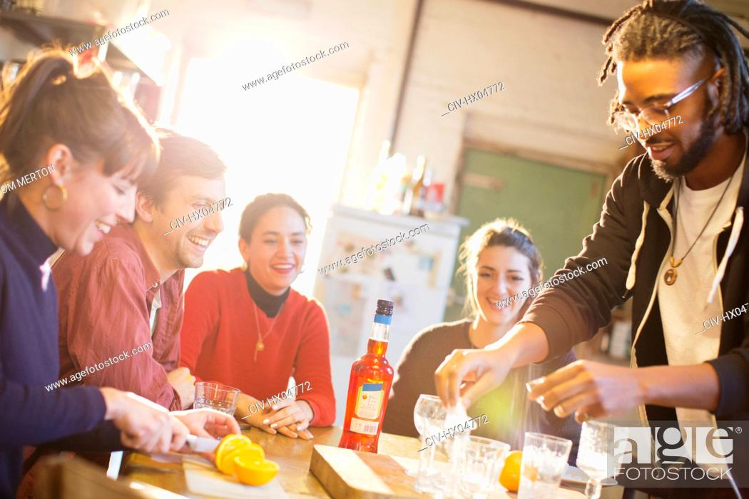 Stock Photo: Young adult friends making cocktails at kitchen table.