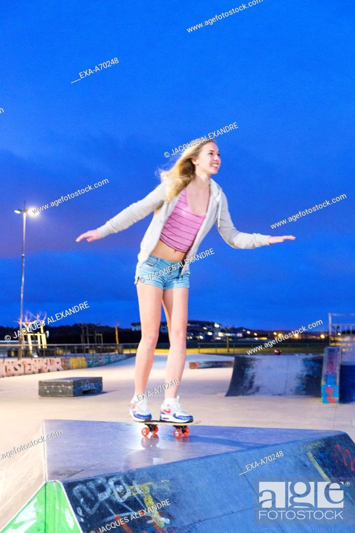 Imagen: Young woman with skateboard at night.