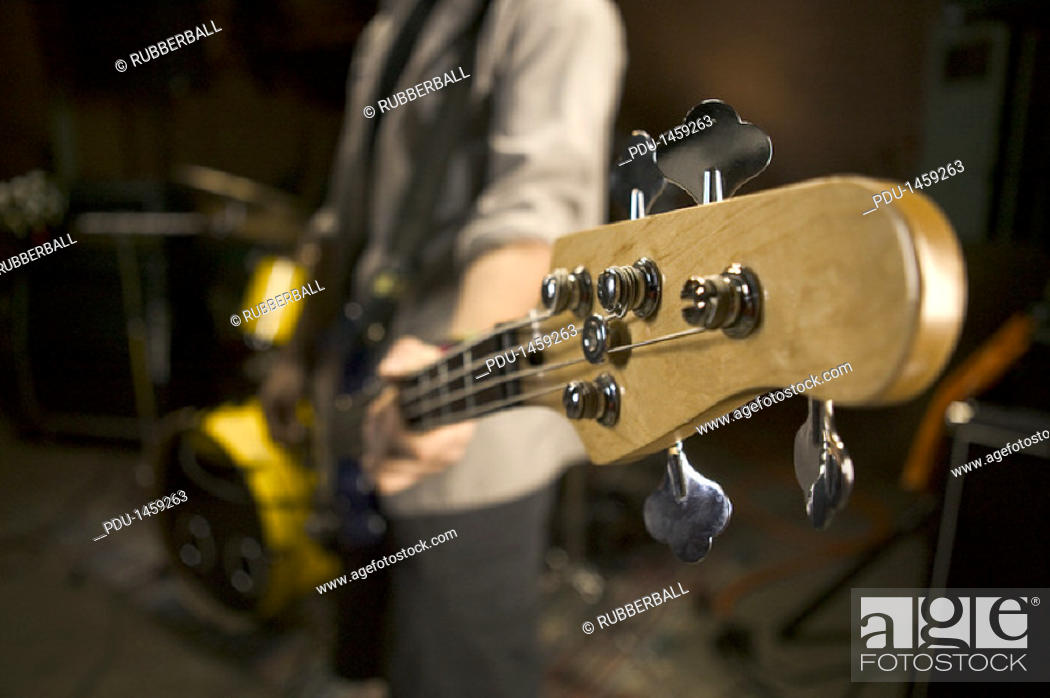 Stock Photo: teenage lifestyle shot of a male guitar player as he practices with his rock band.