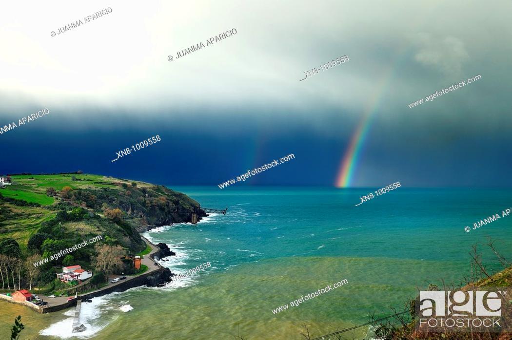 Stock Photo: Cargadero de Mioño y playa de Dicido Cantabria con el arco iris de fondo, en un día de tormenta sobre un mar de color esmeralda.