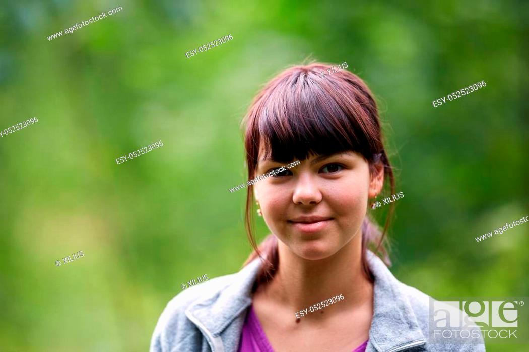 Stock Photo: Candid shot of a young woman outdoor with selective focus near the forest.