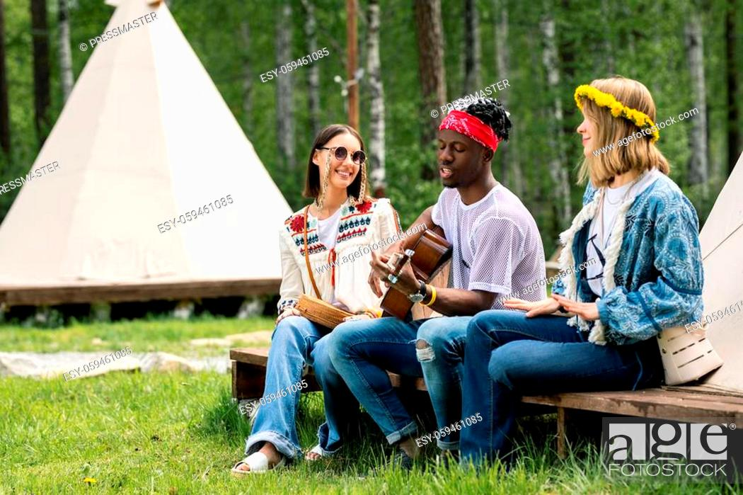 Imagen: Young Black guy in bandana sitting with girls at tent and singing beautiful song at campsite.