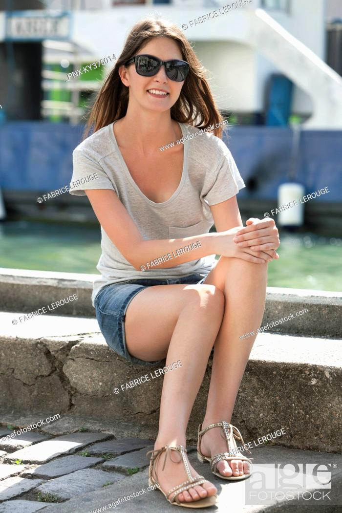 Stock Photo: Woman sitting on the ledge of a canal, Canal St Martin, Paris, Ile-de-France, France.