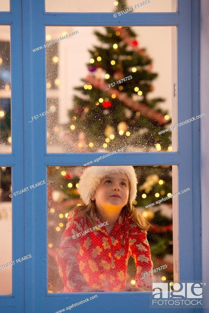 Stock Photo: Young girl looking out of the window waiting for Santa to arrive.