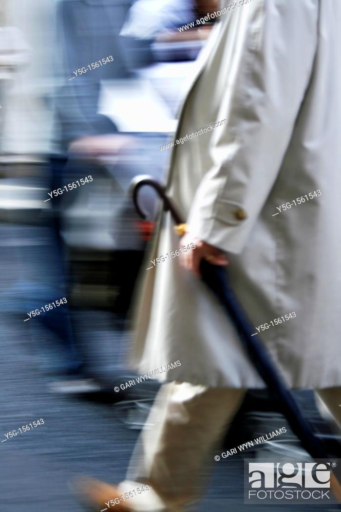 Stock Photo: man with umbrella and holding newspaper in town.