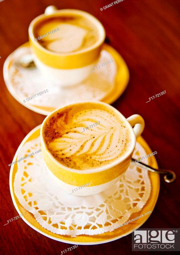 Stock Photo: a beautiful looking cappucino with fancy leaf design in the foam.