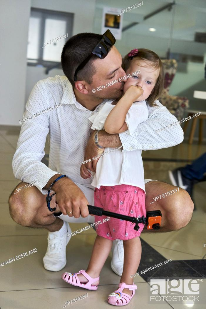 Stock Photo: father kissing toddler daughter indoors, holding action camera in hand.