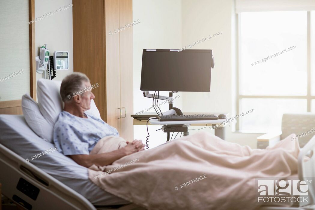 Stock Photo: Caucasian patient sitting in hospital bed.
