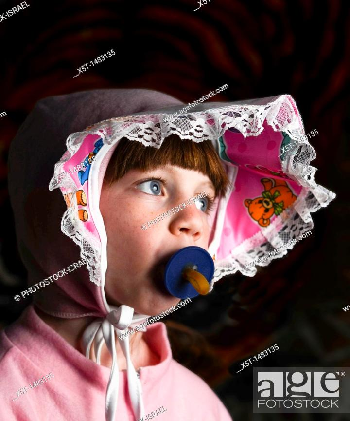 Stock Photo: Young girl of 6 dressed up as a baby with pacifier in her mouth.