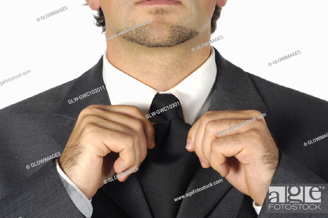 Stock Photo: Close-up of a businessman adjusting his tie.