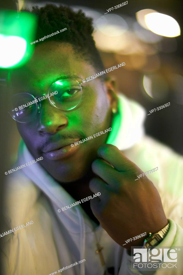 Stock Photo: young intimidated African man at night in green lights, in Munich, Germany.